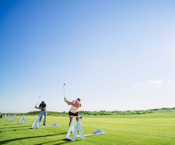 Man And Woman Hitting Golf Balls At The Palmilla Beach Golf Driving Range