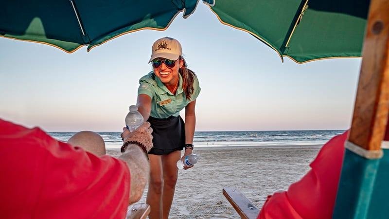 Palmilla Beach Resort's VIP Beach Services Woman Handing A Bottle Of Water To Beach Tourist