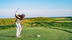 Man Is In A Full Back Swing About To Tee Off On Palmilla Beach Golf Course With Gulf Of Mexico In The Background